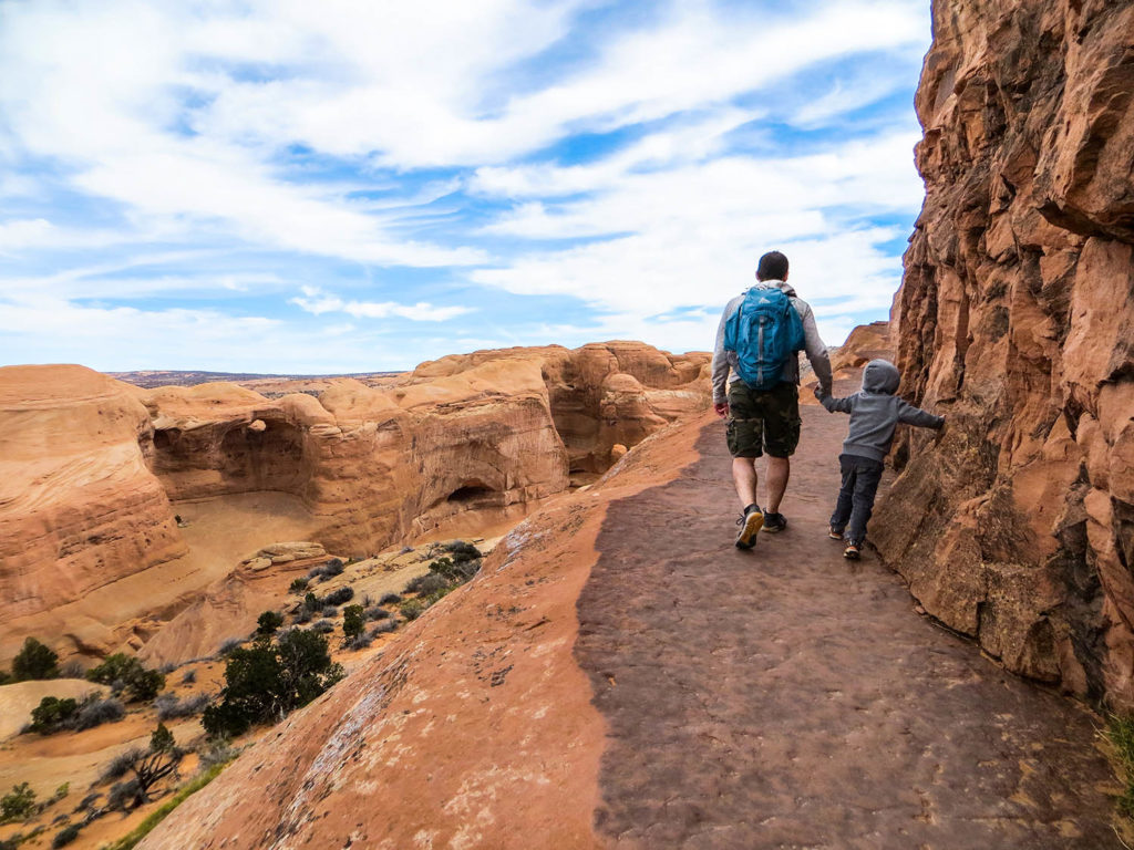Father and son hiking a narrow trail to Delicate Arch