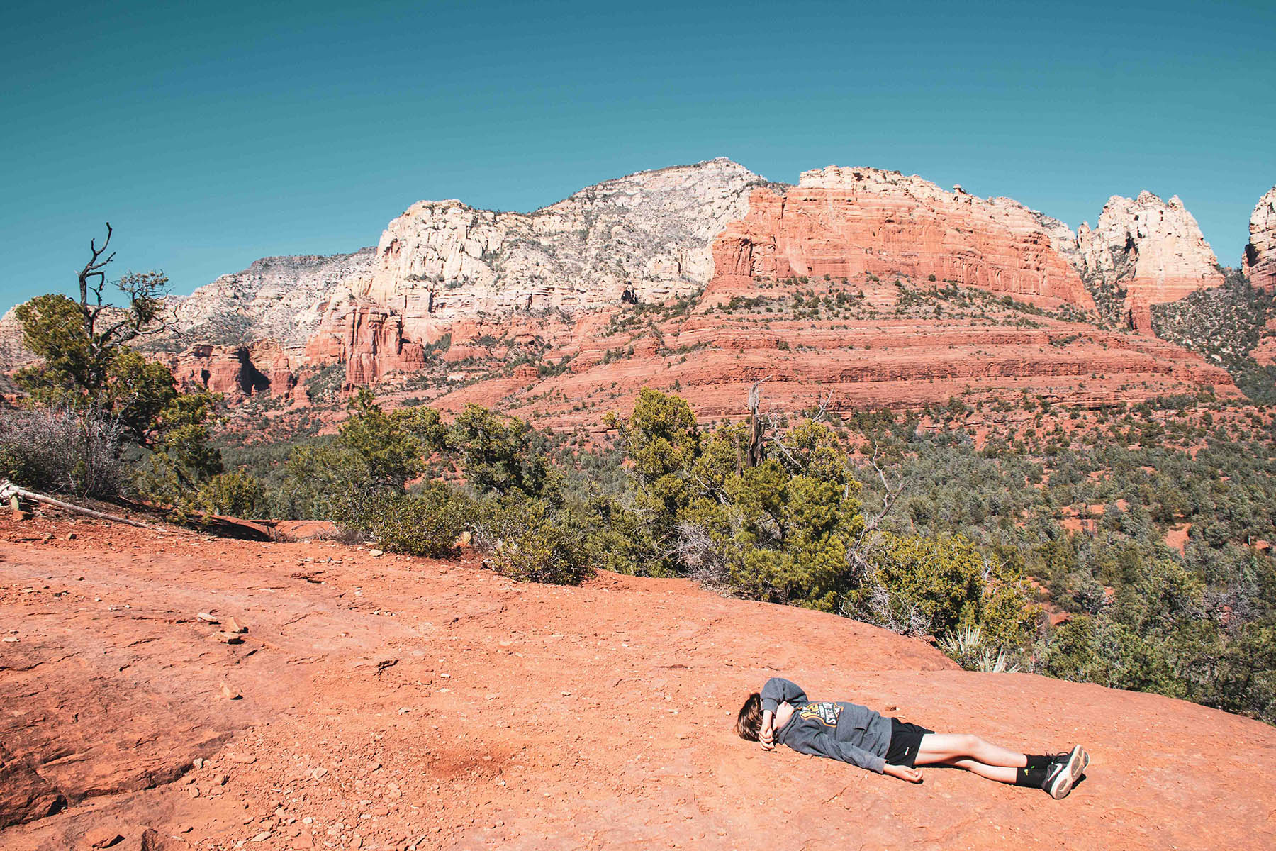 Photo of a young hiker laying down on the trail